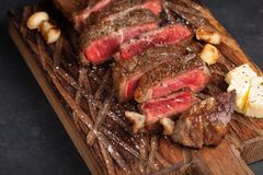 Closeup ready to eat steak new York beef breeds of black Angus with herbs, garlic and butter on a wooden Board. The finished dish. For dinner on a dark stone Royalty Free Stock Photography
