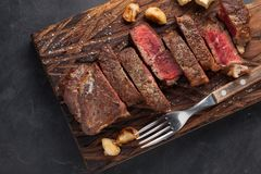 Closeup ready to eat steak new York beef breeds of black Angus with herbs, garlic and butter on a wooden Board. The. Finished dish for dinner on a dark stone Royalty Free Stock Photo