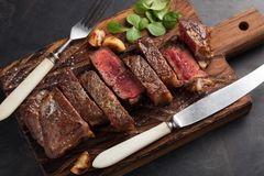 Closeup ready to eat steak new York beef breeds of black Angus with herbs, garlic and butter on a wooden Board. The finished dish. For dinner on a dark stone Royalty Free Stock Images