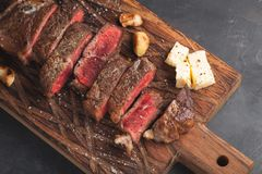 Closeup ready to eat steak new York beef breeds of black Angus with herbs, garlic and butter on a wooden Board. The finished dish. For dinner on a dark stone Stock Photo