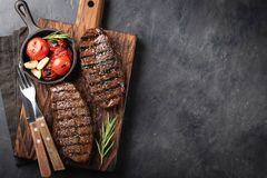 Closeup ready to eat steak Top Blade beef breeds of black Angus with grill tomato, garlic and on a wooden Board. The. Finished dish for dinner on a dark stone royalty free stock photography