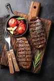 Closeup ready to eat steak Top Blade beef breeds of black Angus with grill tomato, garlic and on a wooden Board. The finished dish. For dinner on a dark stone stock images