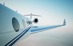 Closeup of realistic photo white, luxury generic design private jet flying over the clouds.Modern airplane and empty blue sky on b Royalty Free Stock Images