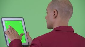Closeup rear view of happy bald multi ethnic businessman using digital tablet. Studio shot of handsome bald multi ethnic businessman against chroma key with stock video footage