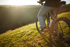 Closeup of rear wheel sports bike. race mountainbike on the hill. Legs. Shoes. Detail of the bicycle. Wheel and bottle. Green field and grass. Travel in the Stock Photography
