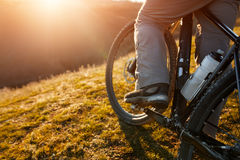 Closeup of rear wheel sports bike. race mountainbike on the hill. Legs. Shoes. Detail of the bicycle. Wheel and bottle. Green field and grass. Travel in the Stock Images