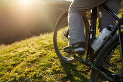 Closeup of rear wheel sports mountainbike rides on the hill. Legs and shoes. Detail of the bicycle. Wheel. Landscape with field and sun. Green grass. Travel in Stock Photo