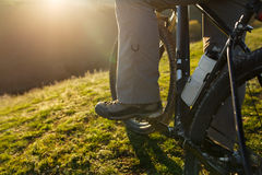 Closeup of rear wheel sports mountainbike rides on the hill. Legs and shoes. Detail of the bicycle. Wheel. Landscape with field and sun. Green grass. Travel in Royalty Free Stock Photos