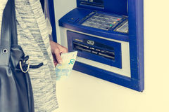Closeup of receiving money from atm. Withdrawing funds Royalty Free Stock Photo