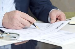Closeup of recruiter`s hands holding resume to approve one. Concept of searching employees stock photo