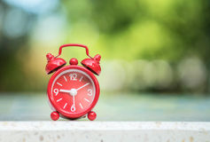 Closeup red alarm clock display seven hours and fifteen minutes on screen on blurred marble desk and park view background Royalty Free Stock Photo