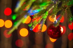 Closeup of a red ball on a christmas tree. Multi-colored bokeh