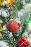 Closeup of red ball hanging from a decorated Christmas tree. Royalty Free Stock Photography