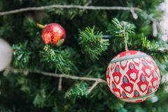 Closeup of red bauble hanging from a decorated Christmas tree. royalty free stock photo