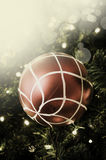 Closeup of red bauble hanging from a decorated Christmas tree. R Royalty Free Stock Photography