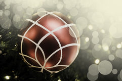 Closeup of red bauble hanging from a decorated Christmas tree. R Royalty Free Stock Photo