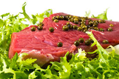 Closeup of raw beef decorated with green pepper grains Stock Image
