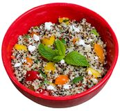 Tri-color quinoa cooked. Closeup on red bowl with tri-color vegan quinoa salad isolated on white - quinoa is a pseudograin that has all nine essential amino Stock Image