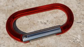 Closeup of a Red Carabiner Resting on Rock Royalty Free Stock Photo