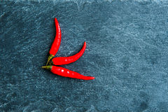 Closeup on red chili peppers on stone substrate Royalty Free Stock Photos
