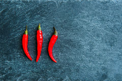 Closeup on red chili peppers on stone substrate Stock Images