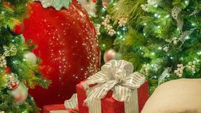 Closeup Red Christmas ornament and present with gold bow and ribbons. royalty free stock image