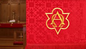 Closeup of red church banner with blurry altar in behind stock image