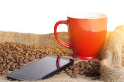 Closeup of red coffee cup next to smart phone Stock Images
