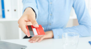 Closeup of red credit card holded by hand. Stock Photos