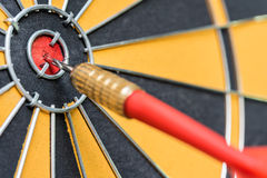 Closeup red dart arrow hitting in target bullseye of dartboard Royalty Free Stock Images