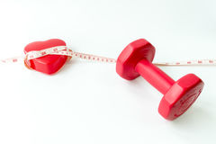 Closeup red dumbbells with measuring tape around red heart. Royalty Free Stock Image