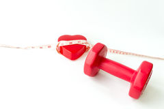 Closeup red dumbbells with measuring tape around red heart. Royalty Free Stock Images