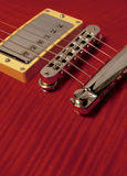 Closeup of red electric guitar. Showing pickup, bridge and detail of the wood grain royalty free stock photography