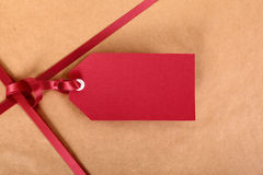Closeup red gift tag and ribbon, brown parcel wrapping paper background Stock Image