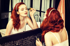Closeup of an red-haired woman applying mascara in mirror Royalty Free Stock Photography