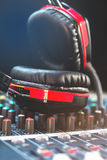 Closeup red headphones and audio mixer on a black background. Royalty Free Stock Photos