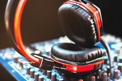 Closeup red headphones and audio mixer on a black background. Royalty Free Stock Photography