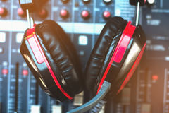 Closeup red headphones and audio mixer. Stock Photo