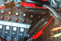 Closeup red headphones and audio mixer. Stock Image
