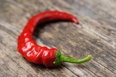Closeup of red Hot chili pepper pod on a wooden desk. In bokeh stock photo