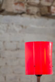 Closeup with red lamp. Red vertical lamp with old walls behind. Stock Photos