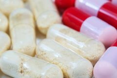 Closeup of red and pink and transparent antibiotics capsule stock image
