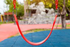 Closeup of red plastic swings. In a childrens playground Royalty Free Stock Photography