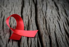 Closeup red ribbon awareness on wooden background. For World Aids day campaign stock photo