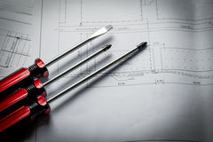 Closeup red screwdriver work equipment with diagram paper plan Royalty Free Stock Image