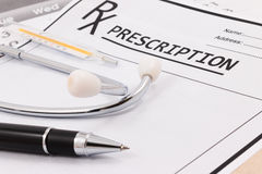 Closeup of red stethoscope, thermometer and pen on a rx prescription. Stock Image