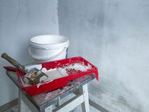 Closeup of a red tray with white paint and brushes and a paint bucket over the light walls. Concept of renewing life and repair royalty free stock photo
