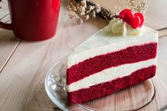 Closeup Red Velvet Cake with glass plate on wooden. Red cup and sketch book background. Suitable for valentine occasion Royalty Free Stock Image