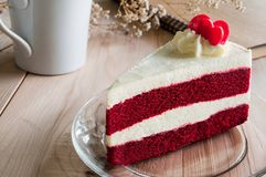 Closeup Red Velvet Cake with glass plate on wooden. White cup and sketch book background. Suitable for valentine occasion Stock Photo