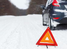 Closeup of red warning triangle with a broken down car Stock Photo